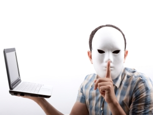 Man with mask holding computer